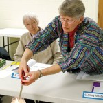 Sister Mary Montgomery lights a candle at the beginning of a Just Matters session she helps lead in Terre Haute, Indiana on migration, theology and the human journey. Sister Joan Matthews, a participant in the sessions, looks on.