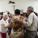 Providence in the Desert's Sister Carol Nolan becomes a part of the community in the rural southern California towns where she lives and serves. Here she greets a couple at Mass at the mission location in Thermal, California, where the largely immigrant population gathers for weekly Mass in a community center because there is no church available.